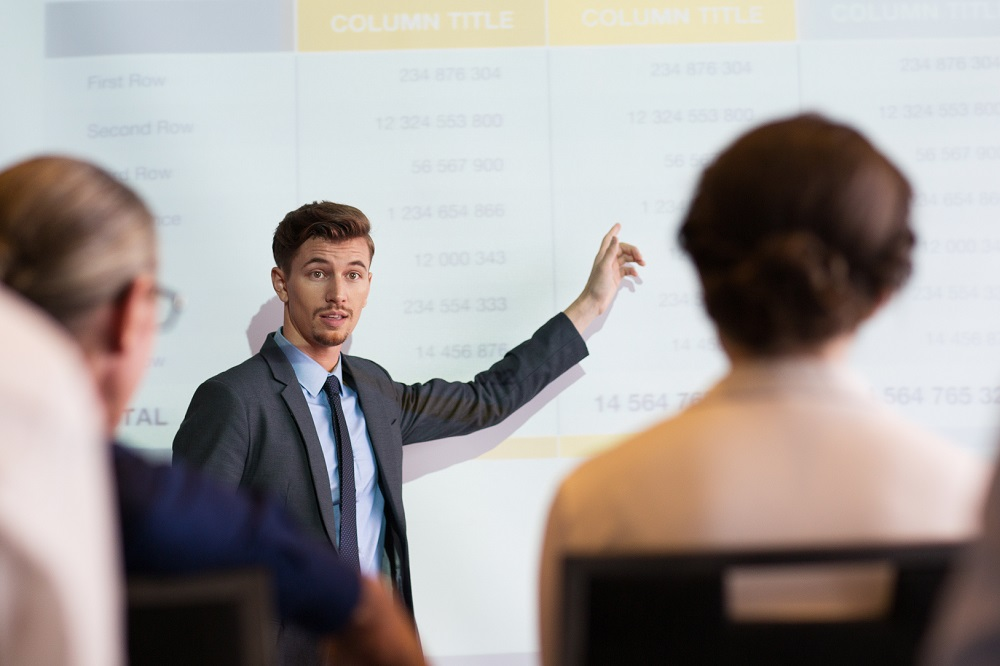 Serious middle-aged businessman standing at projection screen with table and pointing to it while looking and explaining ideas to audience seen partly